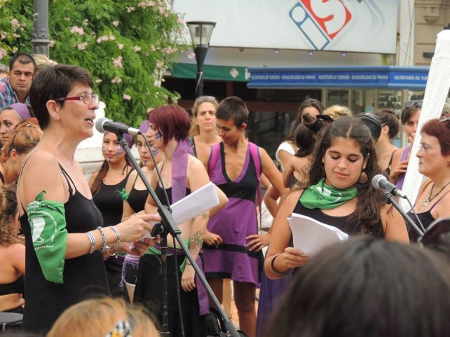 Jorgelina leyendo frente al micrófono en la plaza 1° de Mayo.