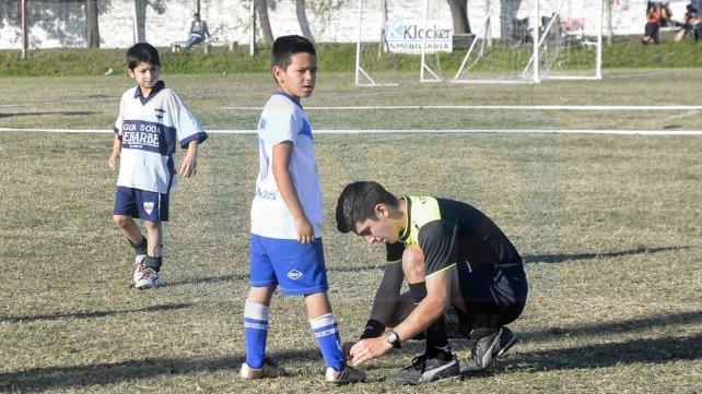El árbitro, Renzo Pitassi, atandole los cordones a un jugador de Sportivo Urquiza.Foto <b>UNO </b>Mateo Oviedo